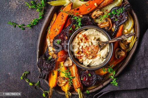 Baked carrots, beets, zucchini and yam with hummus in a dark dish.