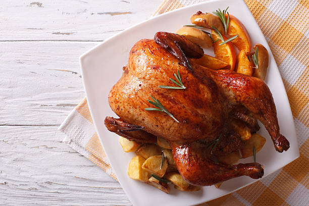 baked whole chicken with oranges on plate. horizontal top view - foto de stock