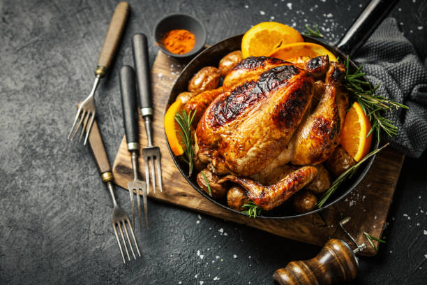 Baked whole chicken with spices on pan Tasty appetizing baked whole chicken with rosemary, potato and spices in pan. Served on wooden board. Christmas chicken. Horizontal. chicken stock pictures, royalty-free photos & images