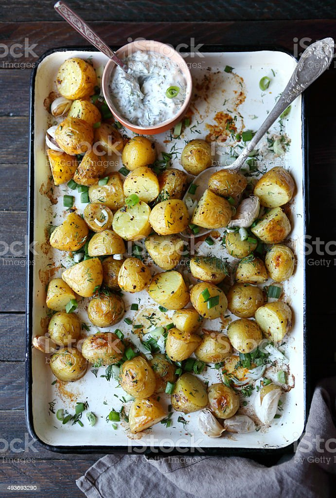 baked young potatoes and chopped greens stock photo