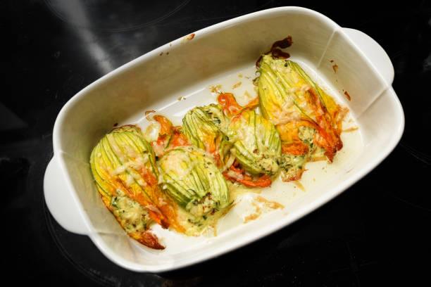 gebackene zucchiniblüten in einem topf auf einem dunklen hintergrund, köstliche gemüse vorspeise, erhöhte ansicht von oben - gefüllte zucchini vegetarisch stock-fotos und bilder