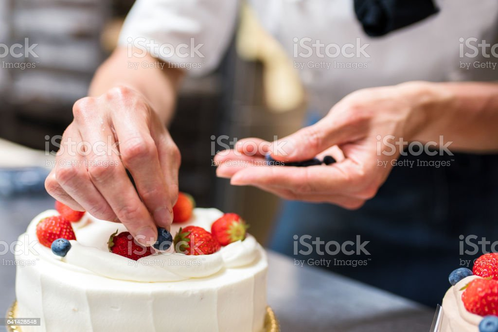 Baker adding blueberries to a cake stock photo