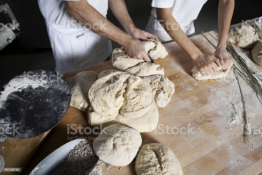 Baker and his son kneading dough royalty-free stock photo