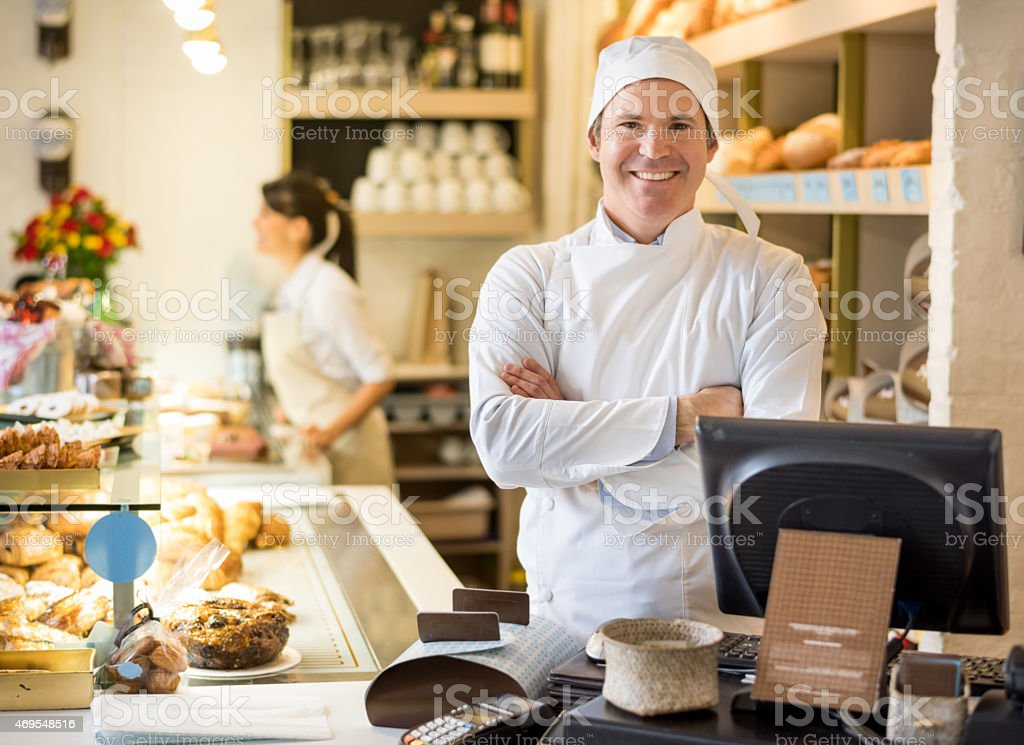 Baker behind the counter at the bakery stock photo