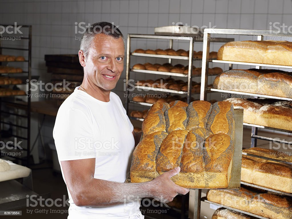 Baker carrying tray of fresh breads  royalty free stockfoto