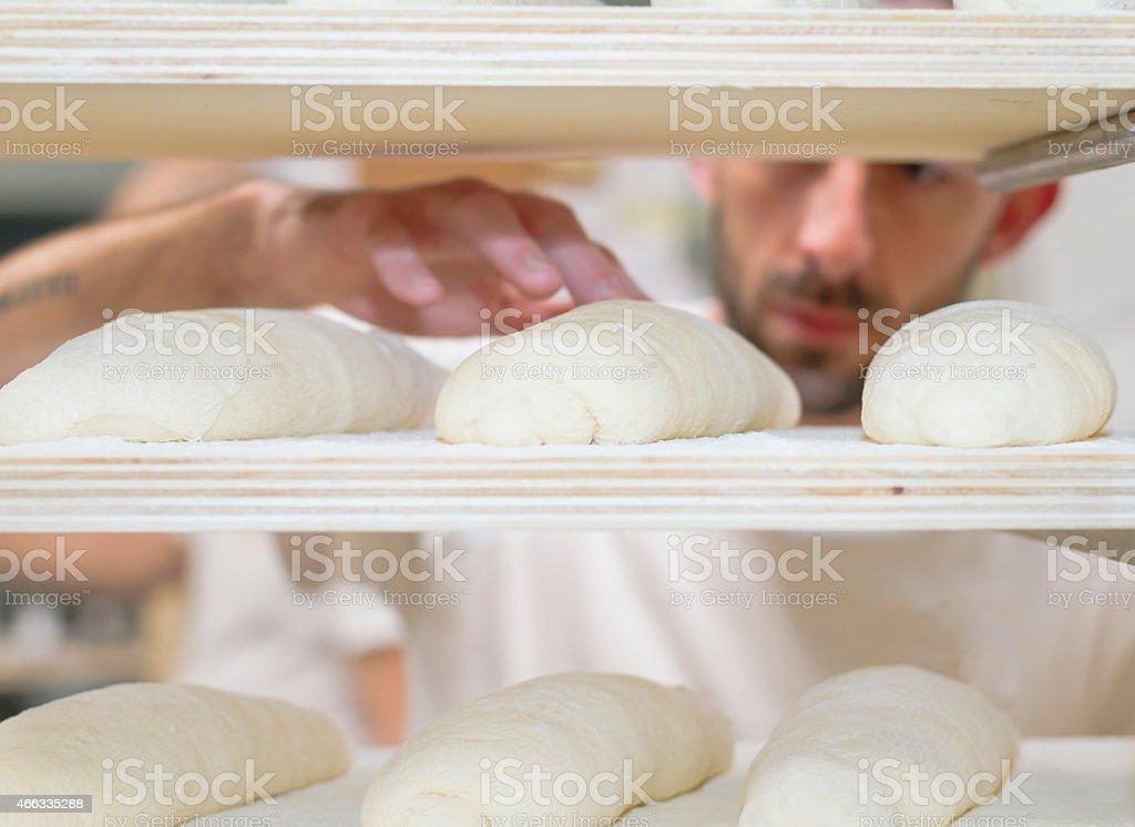 Baker checking bread dough stock photo