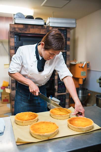 baker cutting a cake - kochkunst stock-fotos und bilder