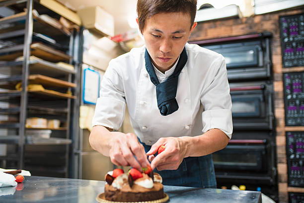 Baker decorating a cake stock photo