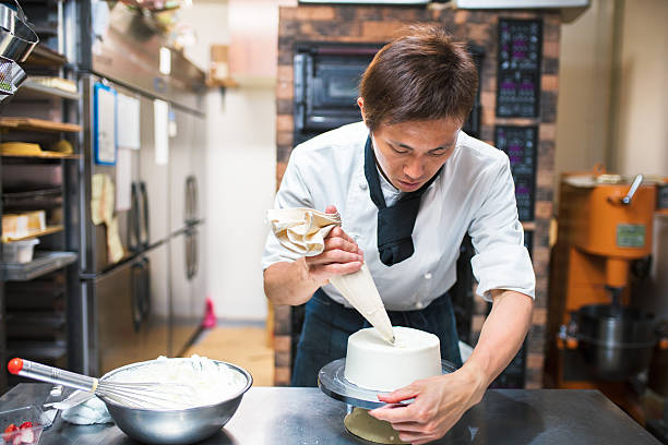 Baker decorating a cake Baker icing a freshly finished cake. Kyoto, Japan. May 2016 decorating a cake stock pictures, royalty-free photos & images