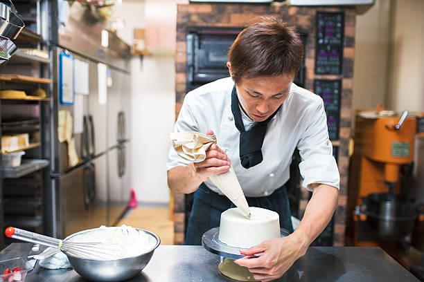 baker dekorieren ein kuchen - kochkunst stock-fotos und bilder