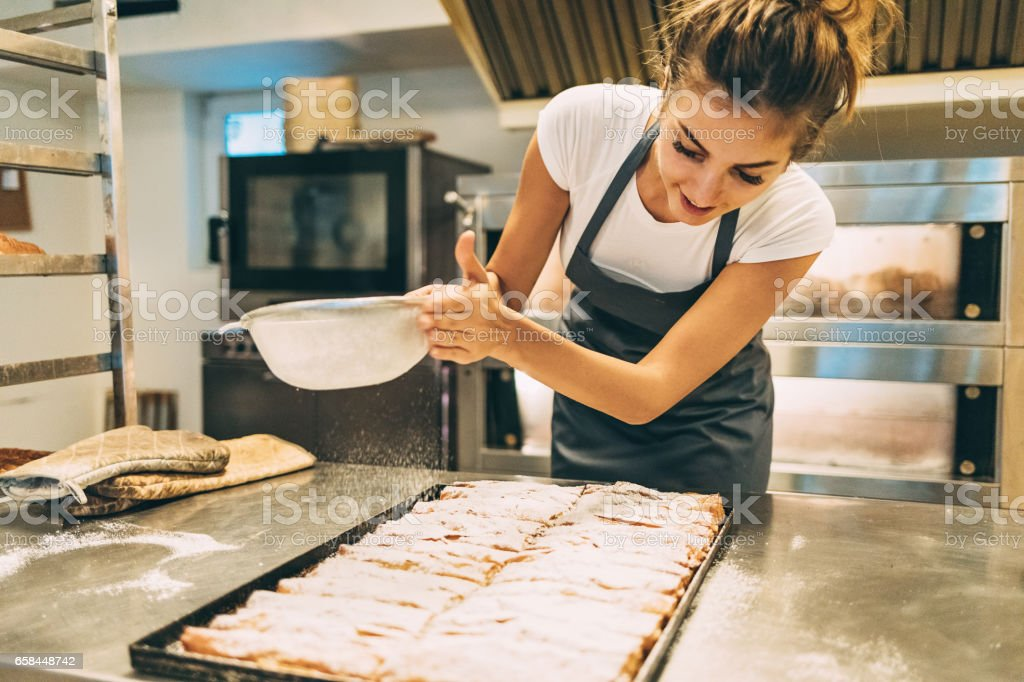 Baker dusting the pastry with powder sugar stock photo