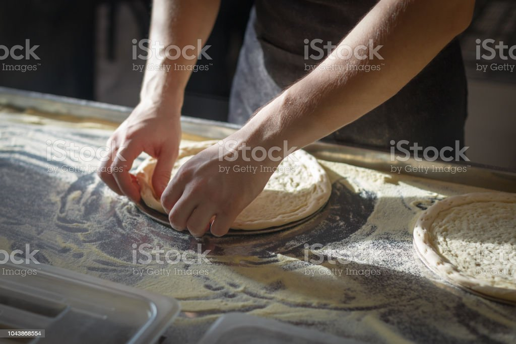Baker forms a round base for pizza making stock photo