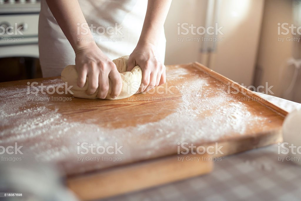 Baker hands kneading dough in flour on table stock photo