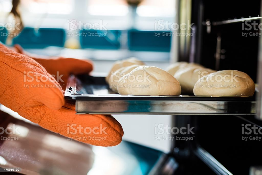 Baker hands with potholder next to metal cookie sheet Baker hands with potholder next to metal cookie sheet with bread in oven 2015 Stock Photo