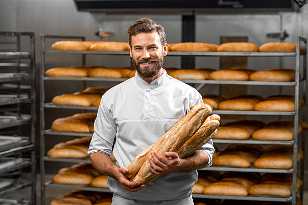 baker holding baguettes at the manufacturing - bakker stockfoto's en -beelden
