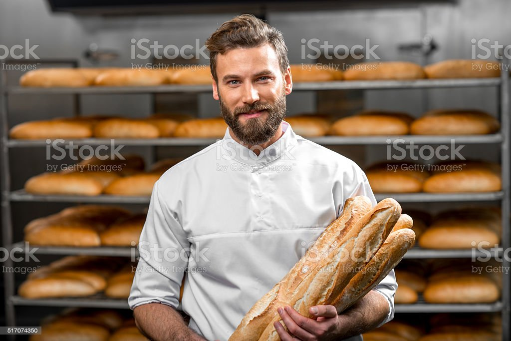 Baker holding baguettes at the manufacturing stock photo