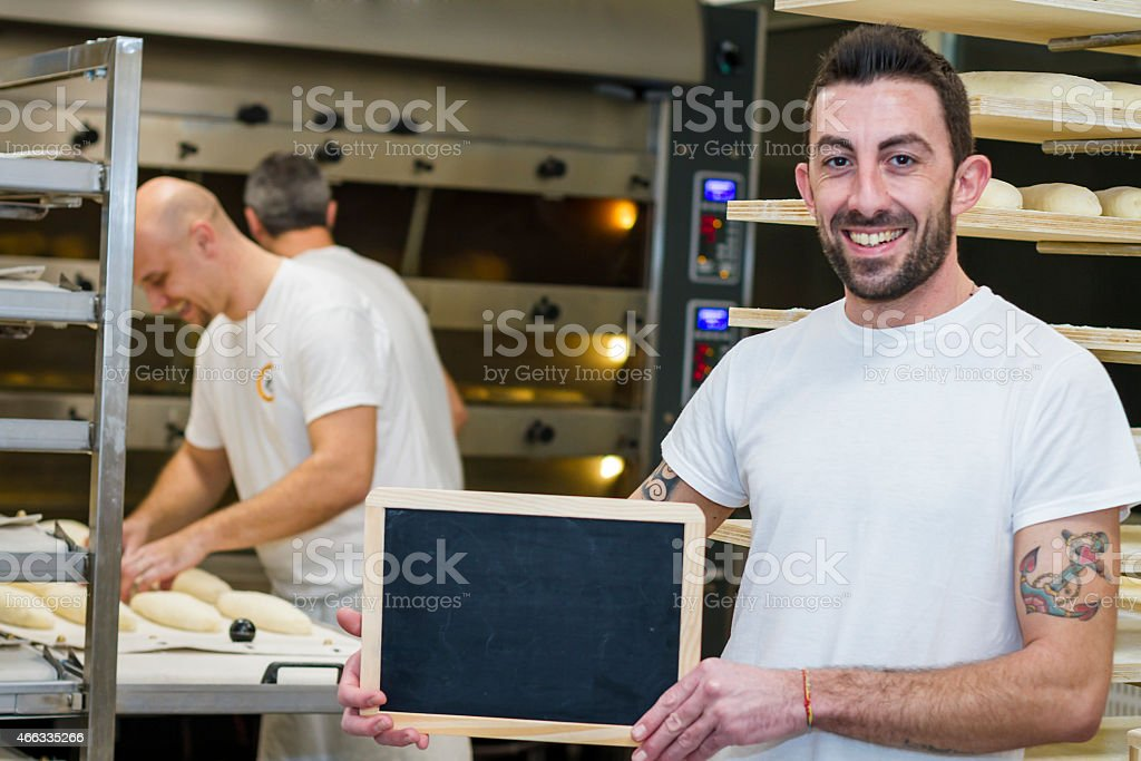 Baker holding blackboard with colleagues in background stock photo