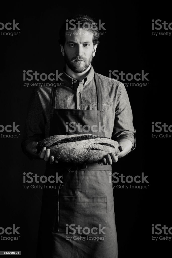 Baker holding bread - Photo