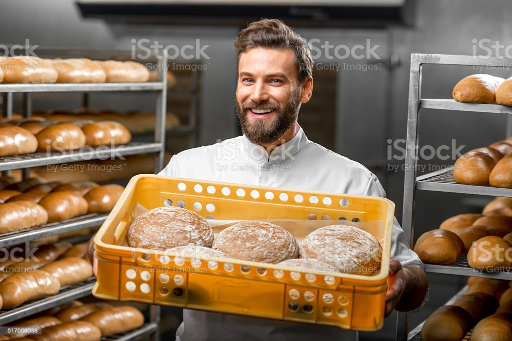 Baker holding breads at the manufacturing stock photo