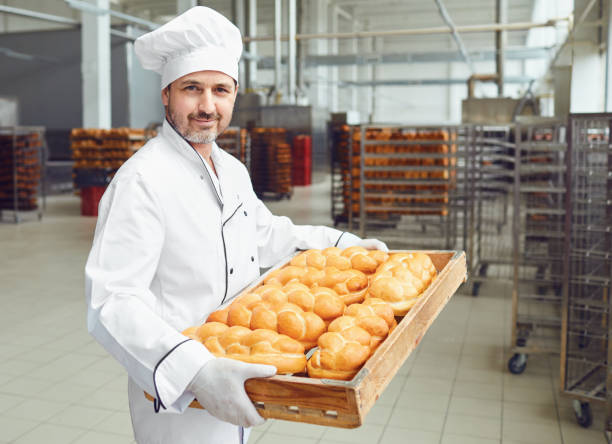 A baker in a bakery against the shelves of bread. stock photo