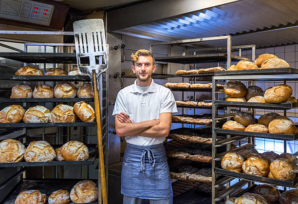 baker in his bakery baking bread - bakker stockfoto's en -beelden