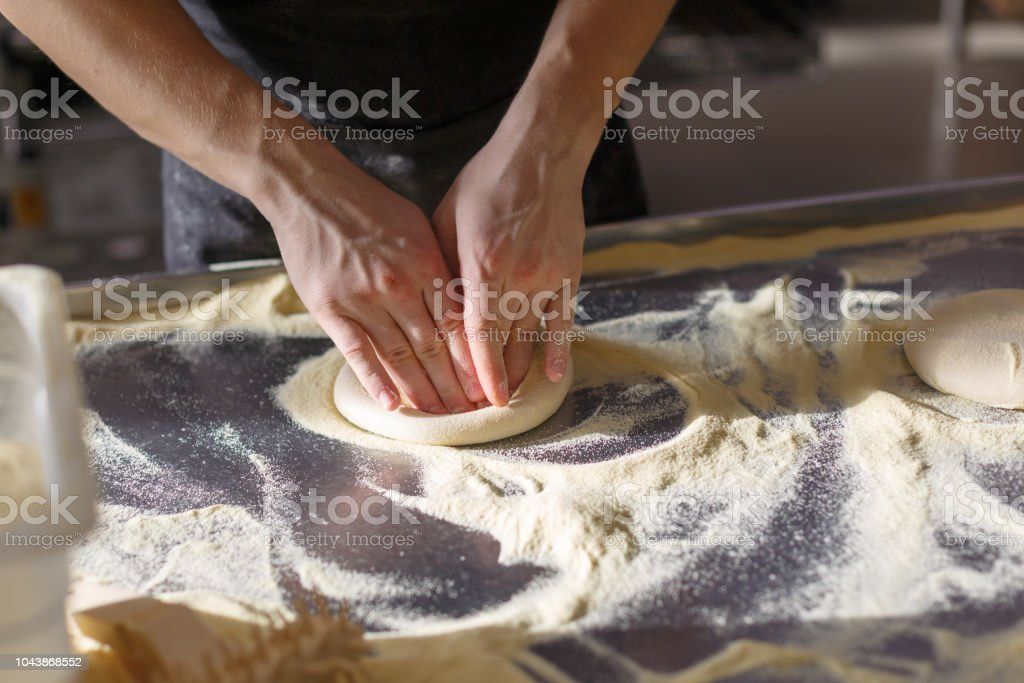 Baker kneads dough for pizza in the kitchen in the restaurant stock photo