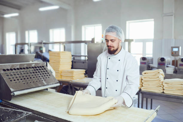 Ein Bäcker macht den Teig auf den Geräten in der Bäckerei – Foto