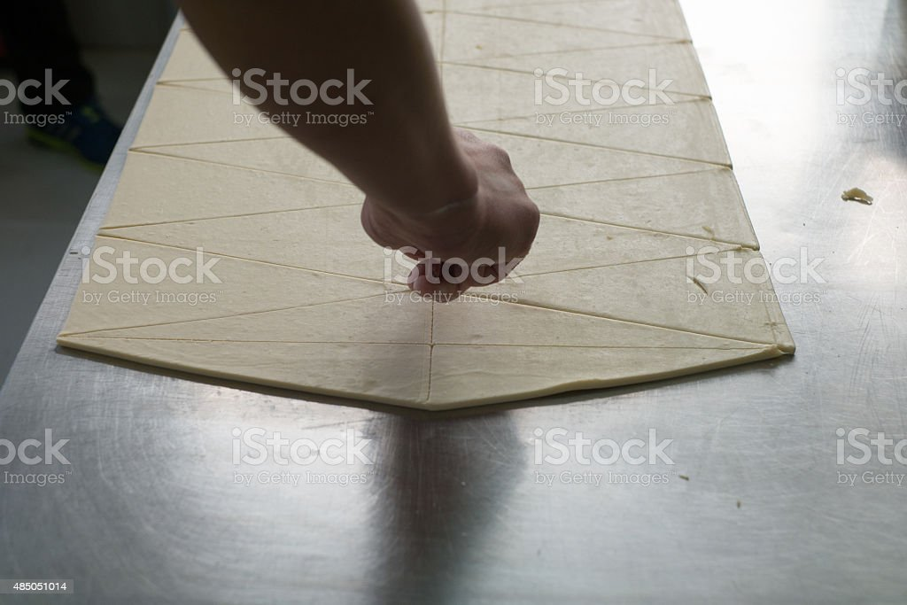 Baker Making Cuts in Croissant Dough stock photo