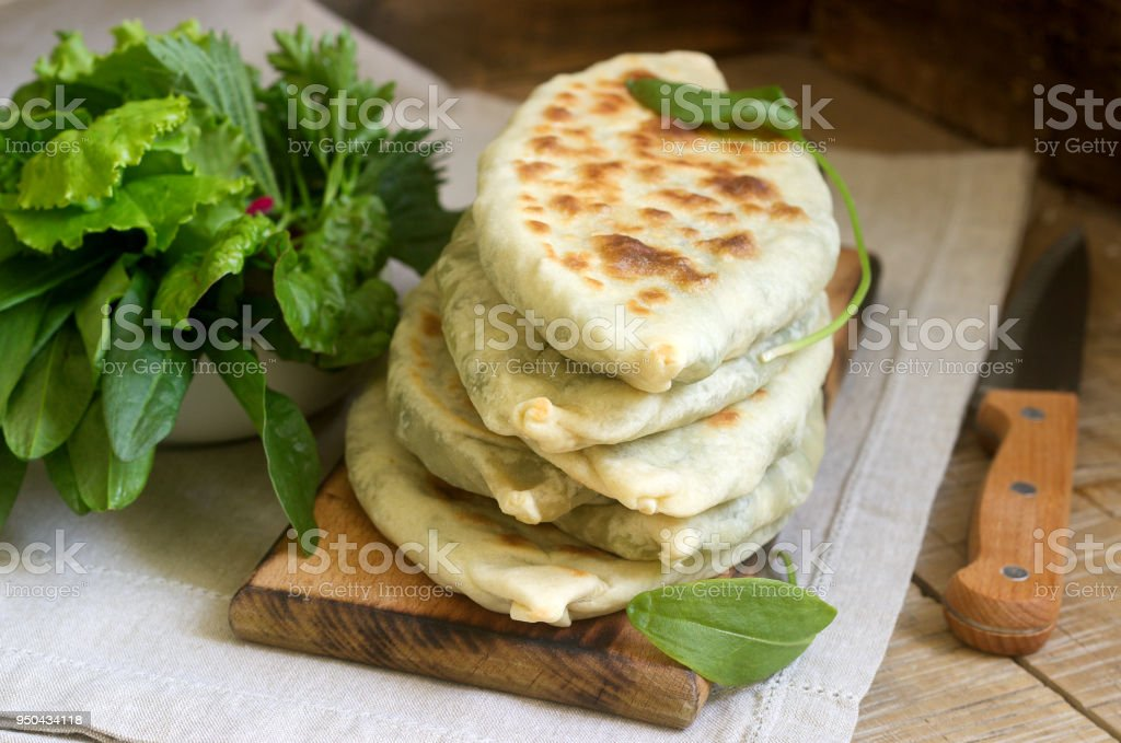 Baker making traditional dish of Armenians from Artsakh Zhingyalov hats is a type of flatbread stuffed with herbs. stock photo