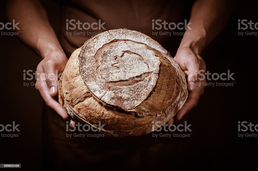 Baker man holding a round bread stock photo