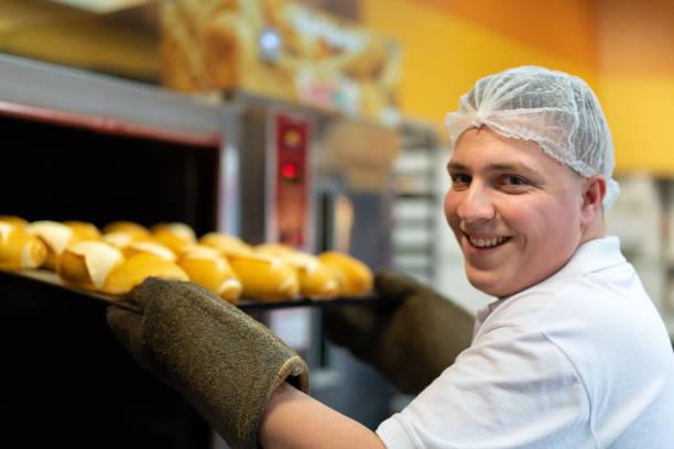 baker man showing delicious bread - panettiere foto e immagini stock