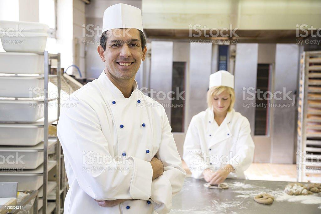 Baker posing in bakery or bakehouse stock photo