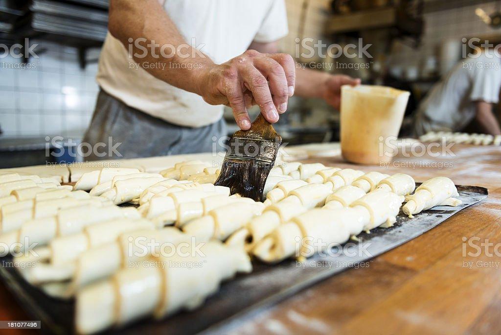 Baker Preparing Croissants In Bakery royalty-free stock photo