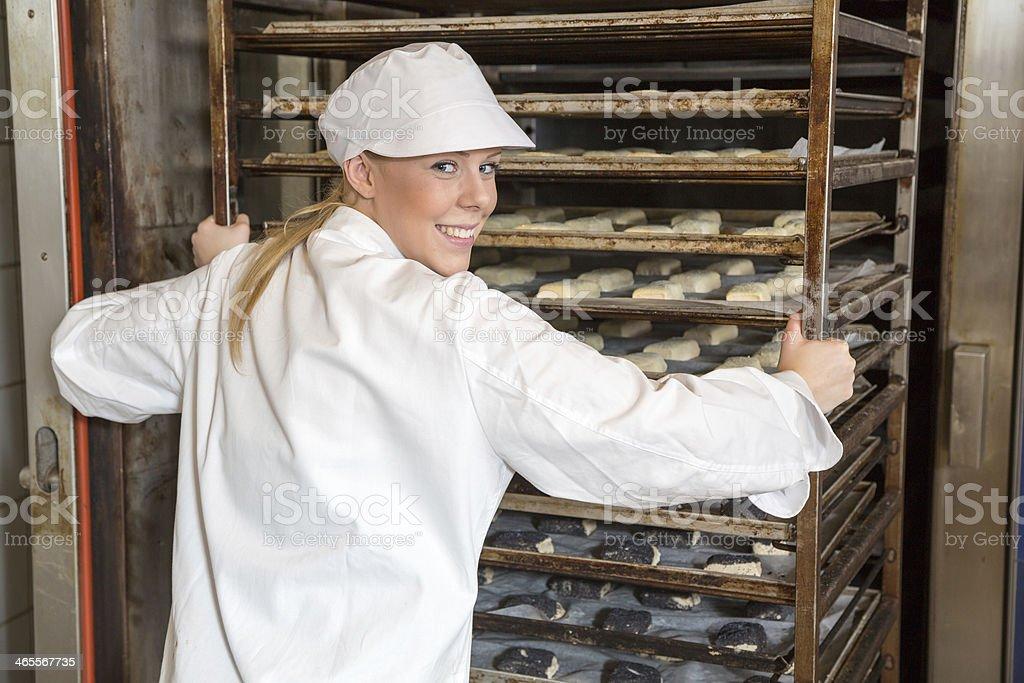 Baker pushing rack full of bread into the oven stock photo