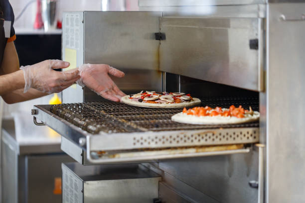 Baker puts raw pizza in an industrial oven stock photo