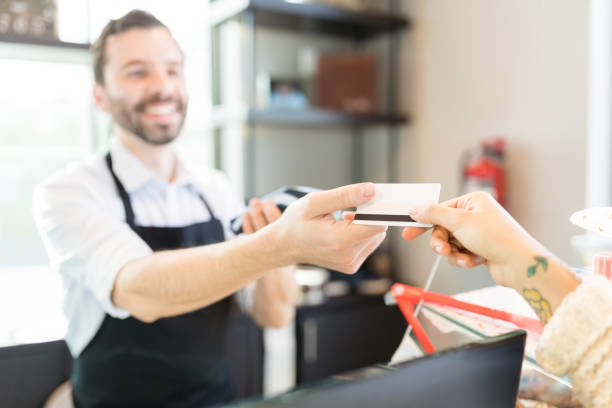 Baker Receiving Card Payment From Woman Hands of salesperson and client passing credit card for payment in bakery convenience stock pictures, royalty-free photos & images