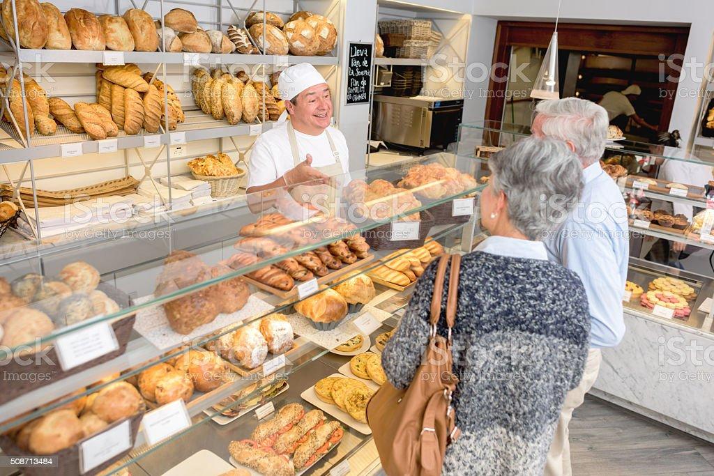 Baker Serving Customers At The Bakery Lizenzfreies Stock Foto