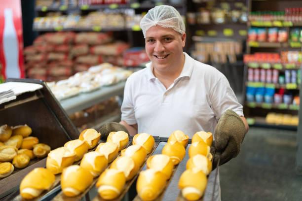 baker showing fresh bread - prodotti supermercato foto e immagini stock