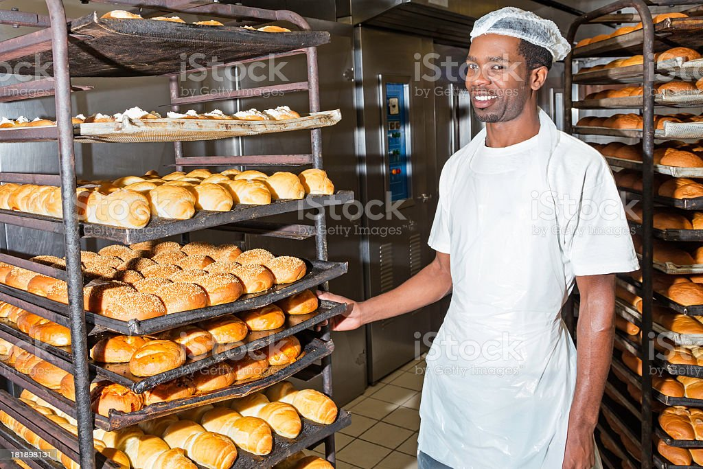 Baker showing his fresh hot bread rolls stock photo