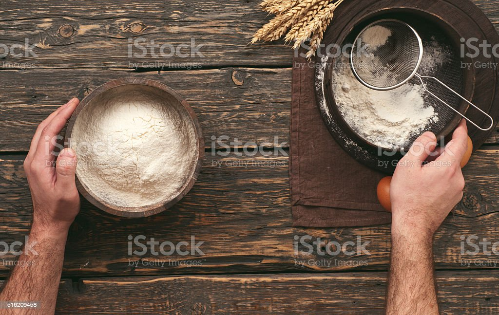 baker sifting the flour stock photo