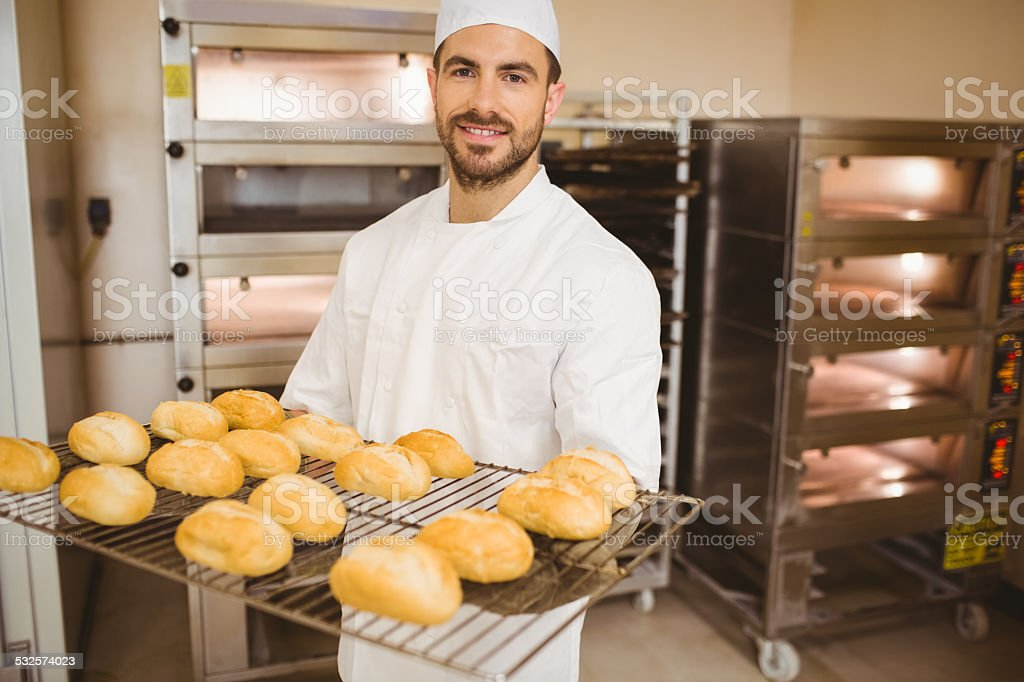 Baker smiling at camera holding rack of rolls stock photo