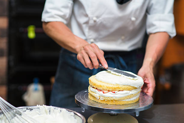 baker spreading cream on a cake - kochkunst stock-fotos und bilder