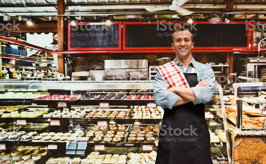 Baker standing in front of bakery store stock photo