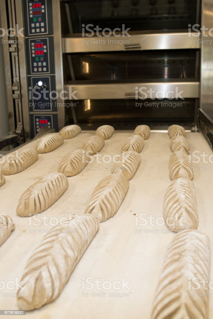 Baker taking fresh baked bread from oven. Manufacturing process stock photo