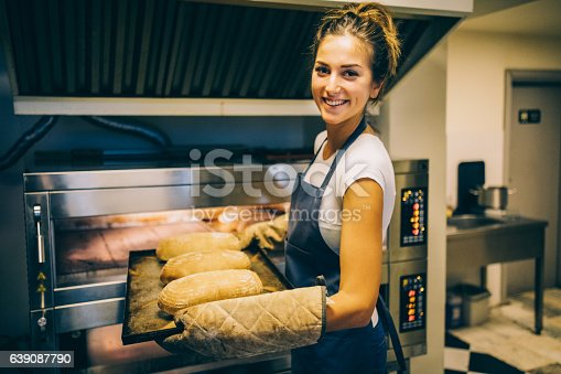 istock Baker taking the freshly baked bread out of the oven 639087790