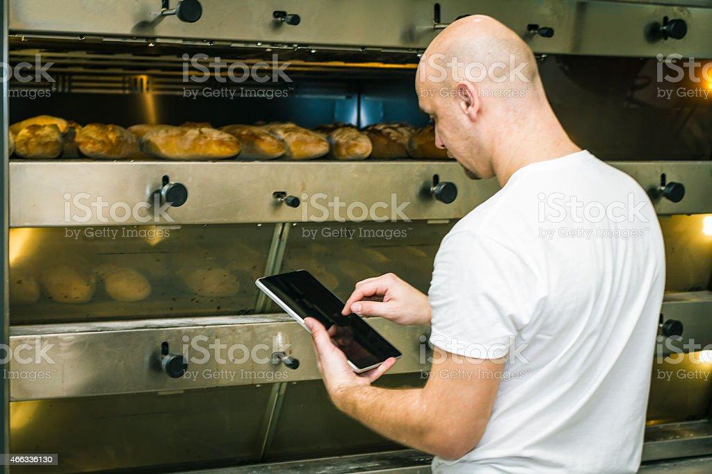 Baker using digital tablet near the oven stock photo