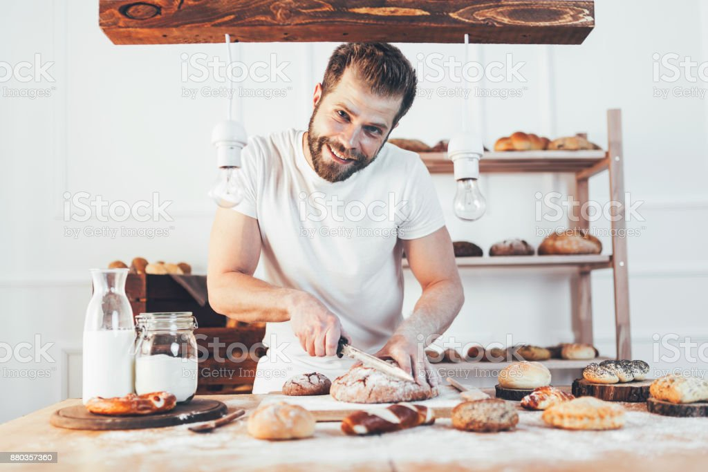 Baker with a variety of delicious freshly baked bread and pastry stock photo