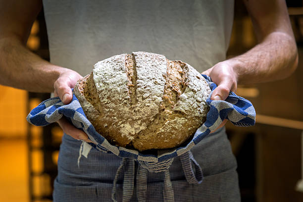 Baker with fresh, warm bread. stock photo