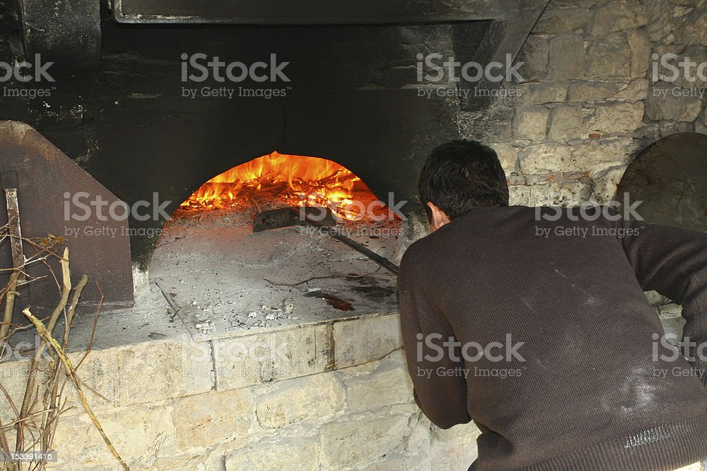 Baker working in oven royalty-free stock photo