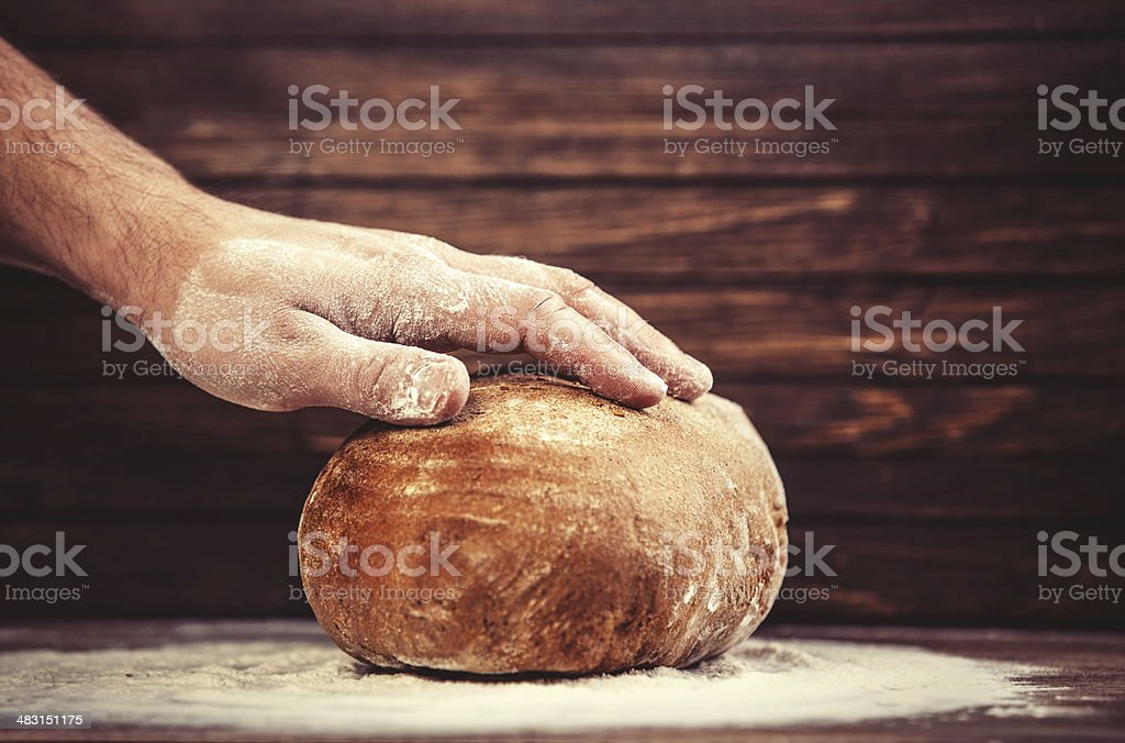 Baker's hands with a bread. stock photo